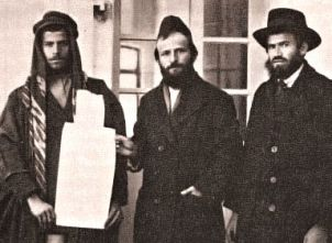 Rabbi Joseph Levi Hagiz (right) and Rabbi Moses Porush (center) holding deed of land purchased from an Arab man.