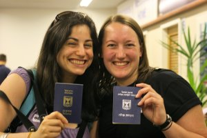 "Immigrants to Israel holding Israeli documents (left, Israeli passport; right Israeli ""immigrant document: teudat oleh."""