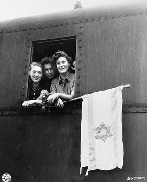 Three young Jewish DPs look out of the window of their train holding a homemade Zionist flag as they depart from Buchenwald (German concentration camp) on the first leg of their journey to Palestine. Photograph by James E. Myers.