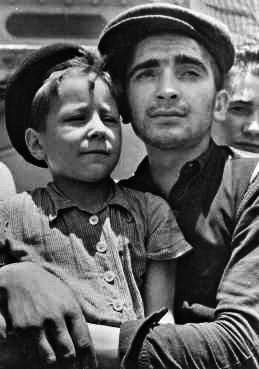 Eight-year-old Yisrael Meir (Lulek) Lau is held by a fellow Buchenwald survivor, Elazar Schiff, as they arrive in Palestine (Israel) aboard the RMS