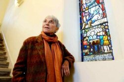 "Professor Eva Haller, one of Jane Haining's ""girls,"" who said she owed her life to her mentor standing by one of the stained glass windows dedicated to the matron at Queen's Park Govanhill Parish Church in Glasgow."