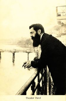 Theodor Herzl observing the Rhine from the balcony of Hotel Les Trois Rois during the Fifth World Zionist Congress in 1901 in Basel, Switzerland. By Ephraim Moses Lilien, (1874–1925). [Public domain].