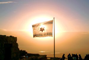 Flag of Israel shines with hope at sunrise on the top of Masada.