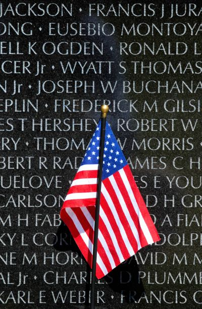 A small American flag stands against the Vietnam Veterans Memorial during a ceremony to add the name of U.S. Army Lt. Col. Taylor to Panel 7W, Line 81 of the memorial in Washington, D.C.