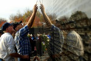 Detail: U.S. veterans point out a familiar name at the Vietnam War memorial following a Veterans Day ceremony, Nov. 11, 2006.