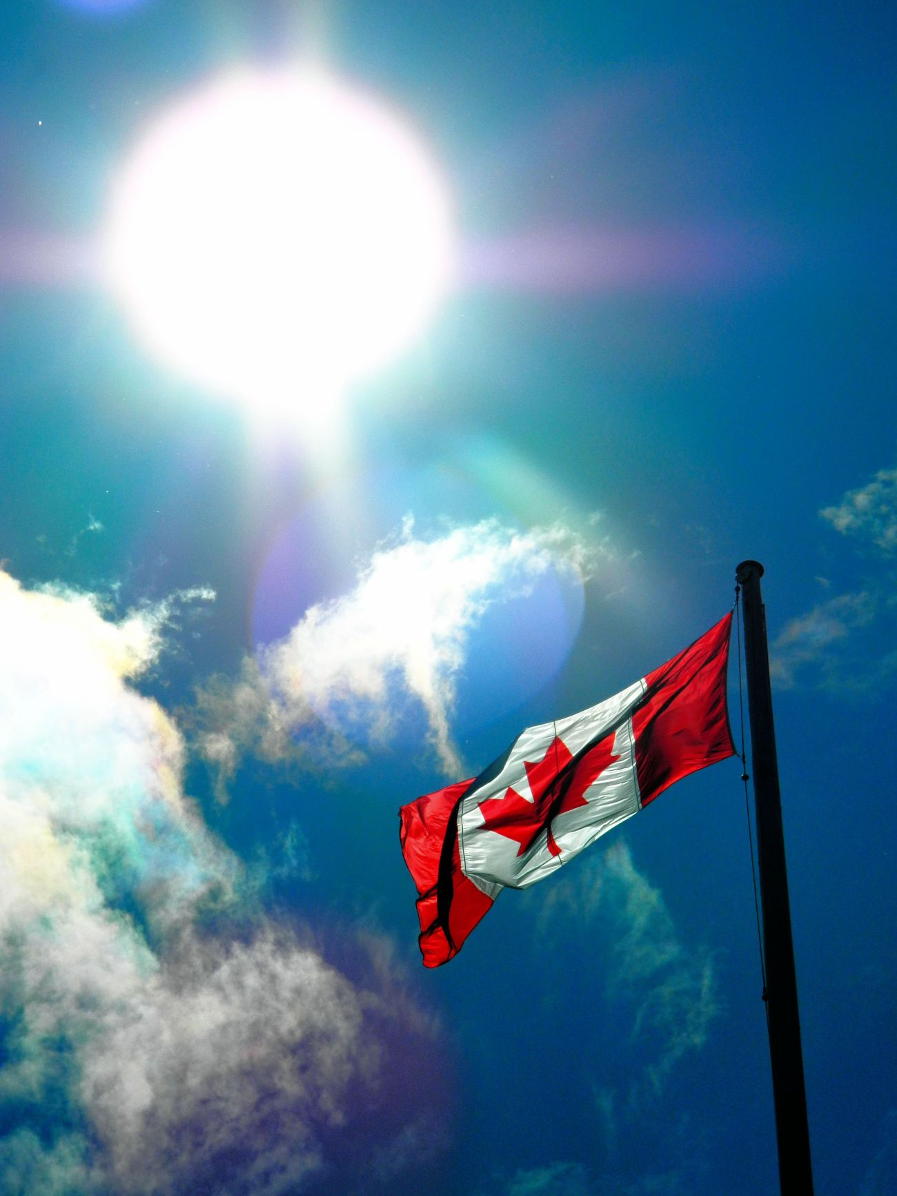 Flag of Canada waves in the halo of the glorious sun.
