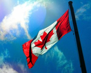 Detail: Flag of Canada waves in the halo of the glorious sun.