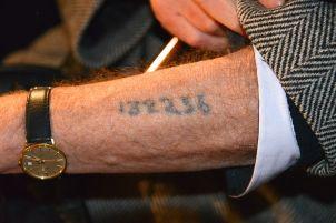 Holocaust survivor shows the prisoner number tattoo.