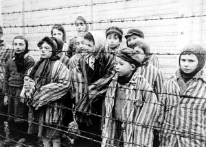 Child survivors of Auschwitz, wearing adult-size prisoner jackets, stand behind a barbed wire fence in Buchenwald concentration camp.